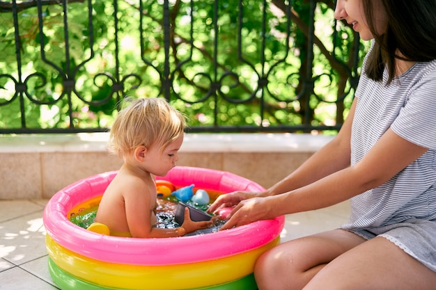 풍선 수영장에 앉아있는 동안 그녀의 손에 국자를 들고 어린 소녀