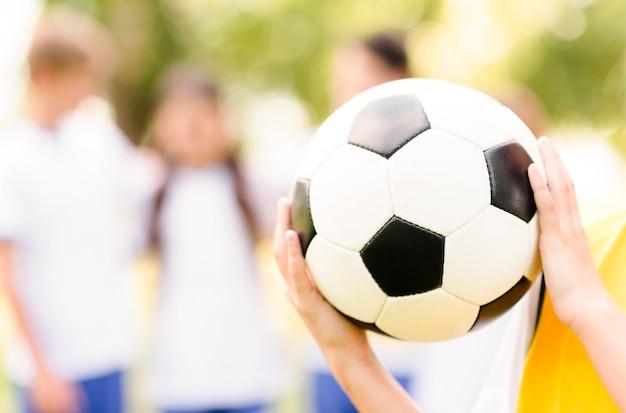 サッカーのクローズアップを保持している小さな女の子