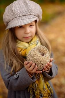 秋の公園で彼女の腕の中で面白いハリネズミを保持している小さな女の子