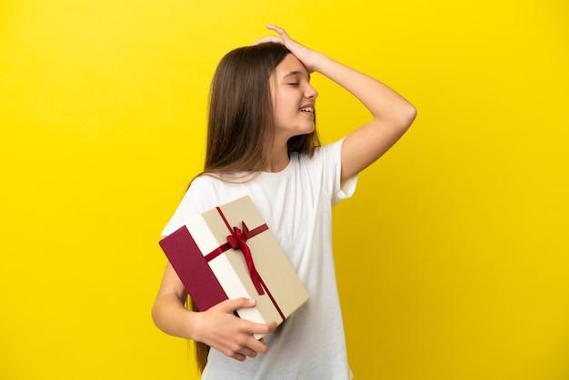 Маленькая девочка, держащая подарок на изолированном желтом фоне, кое-что поняла и намеревается найти решение