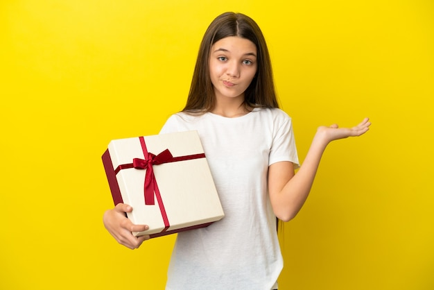 Маленькая девочка держит подарок на изолированном желтом фоне, сомневаясь, поднимая руки