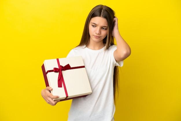Маленькая девочка держит подарок на изолированном желтом фоне, сомневаясь