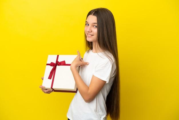 뒤로 가리키는 고립 된 노란색 배경 위에 선물을 들고 어린 소녀