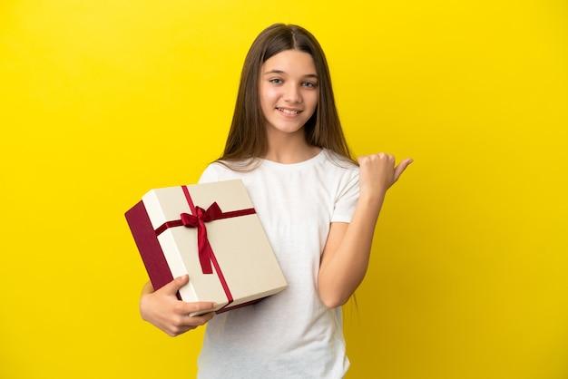 제품을 제시하기 위해 측면을 가리키는 고립된 노란색 배경 위에 선물을 들고 있는 어린 소녀