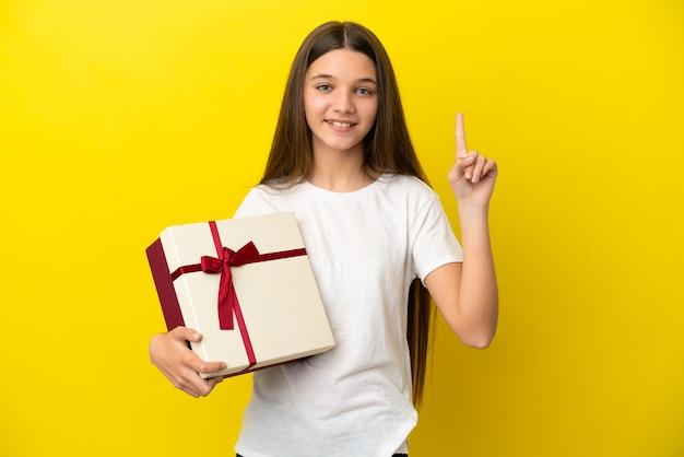 좋은 아이디어를 가리키는 고립된 노란색 배경 위에 선물을 들고 있는 어린 소녀