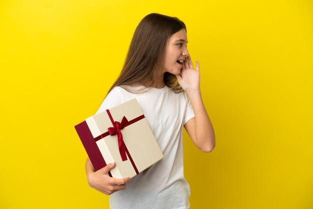 Маленькая девочка держит подарок на изолированном желтом фоне и кричит с широко открытым ртом