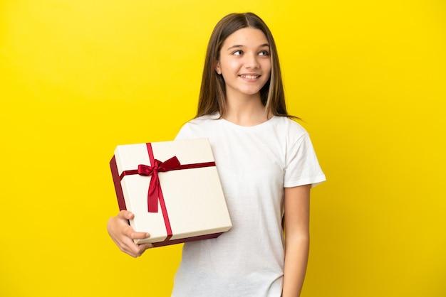 Маленькая девочка держит подарок на изолированном желтом фоне, думая об идее, глядя вверх