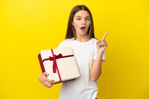 Маленькая девочка держит подарок на изолированной желтой поверхности, думая об идее, указывая пальцем вверх