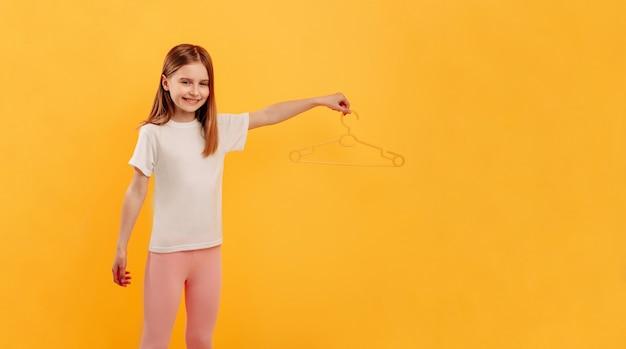 Маленькая девочка держит вешалку на желтом фоне