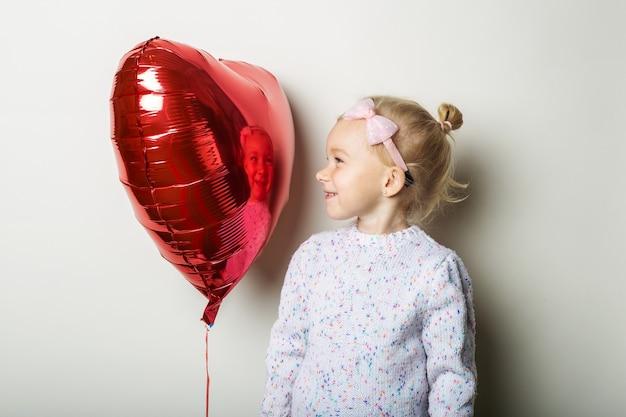 심장 공기 풍선을 들고 어린 소녀와 밝은 배경에 보인다. 발렌타인 데이, 생일에 대한 개념입니다. 배너.