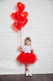 하트 모양의 ballon 들고 어린 소녀