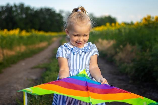 ひまわり畑で凧を持っている少女。