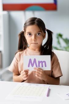 言語療法で文字が書かれた紙を持っている少女