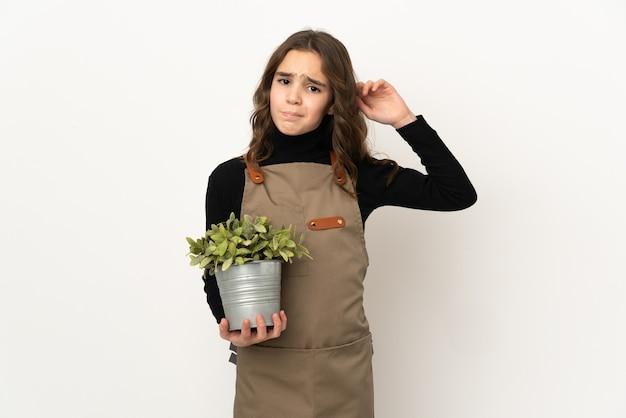 Маленькая девочка держит растение, изолированные на белом фоне, сомневаясь