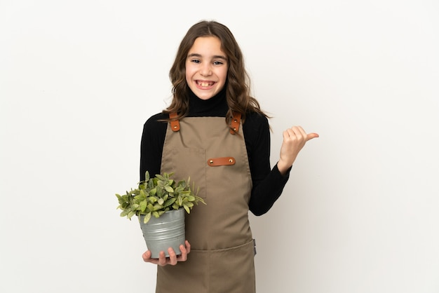 제품을 제시하기 위해 측면을 가리키는 흰색 배경에 고립 된 식물을 들고 어린 소녀