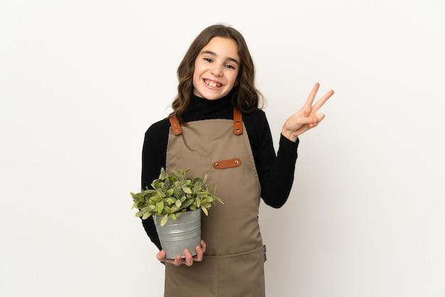 웃 고 승리 기호를 보여주는 흰색 배경에 고립 된 식물을 들고 어린 소녀