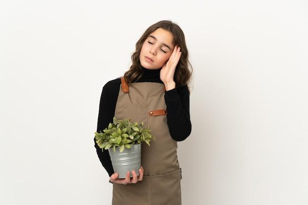 Маленькая девочка держит растение, изолированное на белом фоне с головной болью
