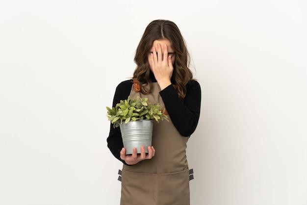 Маленькая девочка держит растение на белом фоне с усталым и больным выражением лица