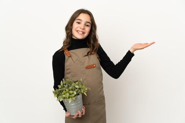 흰색 벽에 고립 된 식물을 들고 어린 소녀가 와서 초대하기 위해 손을 옆으로 확장