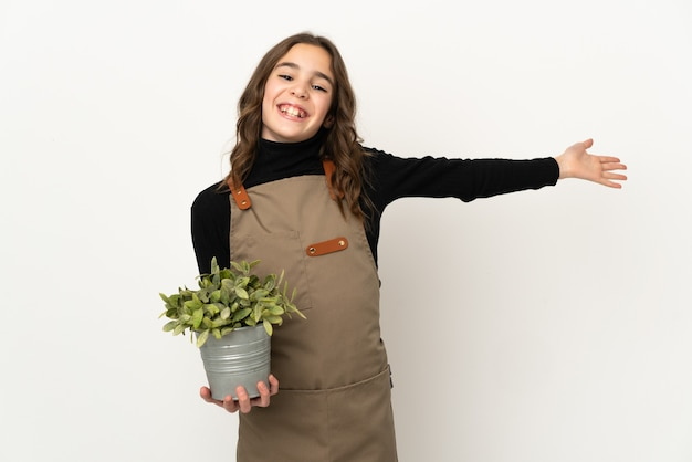 와서 초대하기 위해 손을 옆으로 확장 흰 벽에 고립 된 식물을 들고 어린 소녀