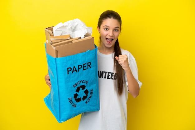 Маленькая девочка держит мешок для переработки, полный бумаги для переработки на изолированном желтом фоне, празднует победу в позиции победителя