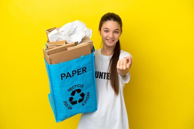 Маленькая девочка держит мешок для переработки, полный бумаги для переработки на изолированном желтом фоне, делая приближающийся жест