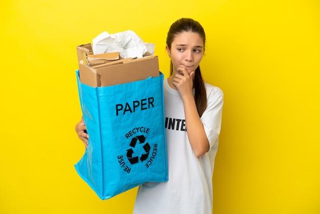 疑いと思考を持っている孤立した黄色の背景の上にリサイクルするために紙でいっぱいのリサイクルバッグを持っている少女