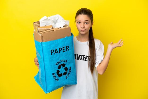 Маленькая девочка держит мешок для переработки, полный бумаги для переработки на изолированном желтом фоне, сомневаясь, поднимая руки