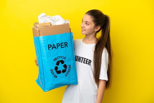 Маленькая девочка держит мешок для переработки, полный бумаги для переработки на изолированном желтом фоне, глядя в сторону