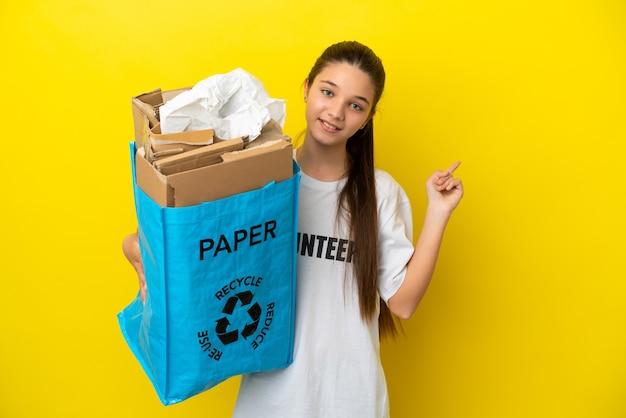 뒤를 가리키는 고립된 노란색 배경 위에 재활용할 종이로 가득 찬 재활용 가방을 들고 있는 어린 소녀