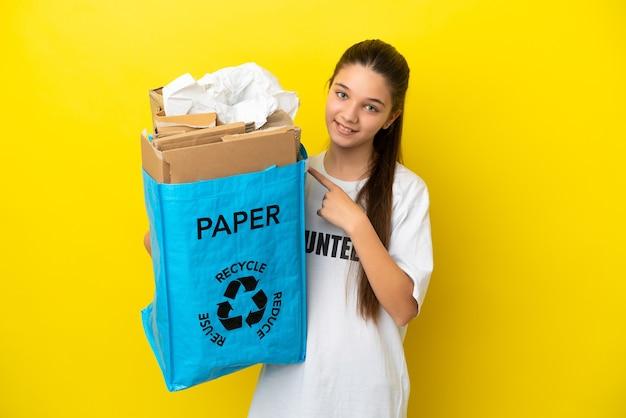 제품을 제시하기 위해 측면을 가리키는 고립된 노란색 배경 위에 재활용하기 위해 종이로 가득 찬 재활용 가방을 들고 있는 어린 소녀