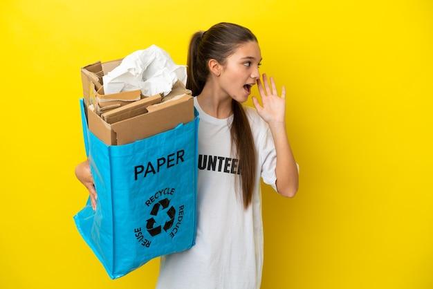 Маленькая девочка держит мешок для переработки, полный бумаги для переработки на изолированном желтом фоне, кричит с широко открытым ртом