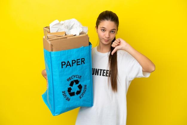ネガティブな表現で親指を下に示す孤立した黄色の背景の上にリサイクルする紙でいっぱいのリサイクルバッグを持っている少女