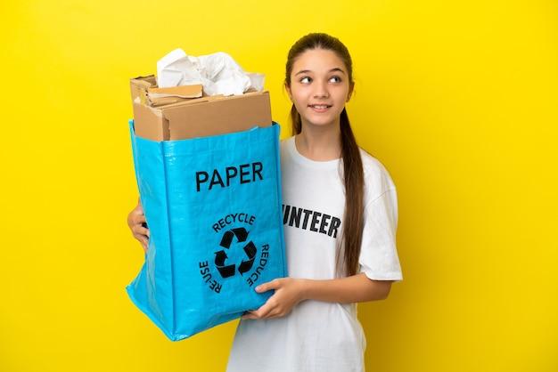 見上げながらアイデアを考えて孤立した黄色の背景の上にリサイクルする紙でいっぱいのリサイクルバッグを持っている少女