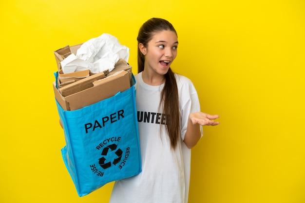 옆을 바라보면서 놀란 표정으로 고립된 노란색 배경 위에 재활용하기 위해 종이로 가득 찬 재활용 가방을 들고 있는 어린 소녀