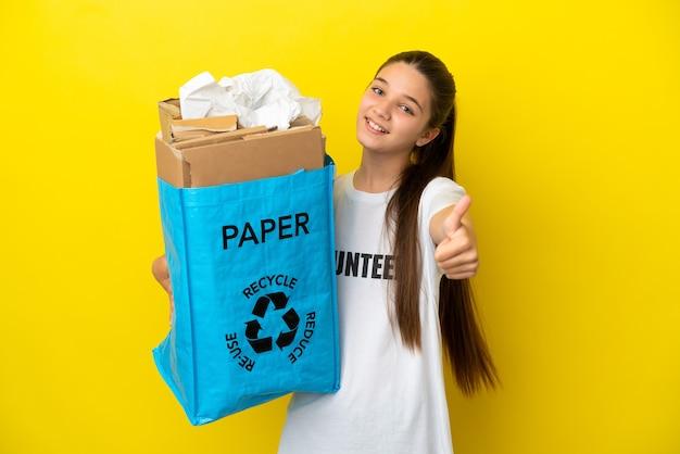 좋은 일이 일어났기 때문에 고립된 노란색 배경 위에 재활용하기 위해 종이로 가득 찬 재활용 가방을 들고 있는 어린 소녀