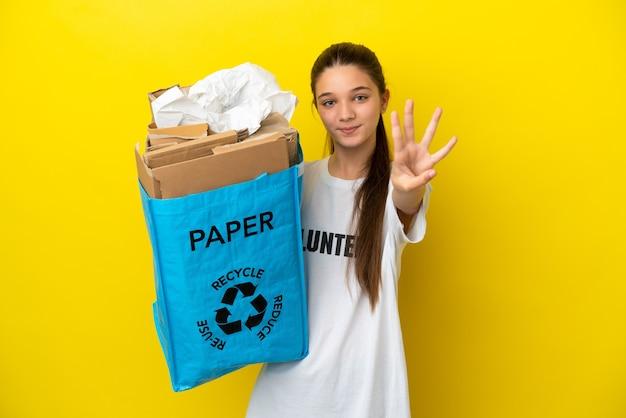 종이로 가득 찬 재활용 가방을 들고 어린 소녀가 고립 된 노란색 벽 행복하고 손가락으로 4 세 이상 재활용합니다.