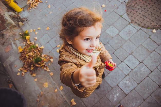 Маленькая девочка держит в руке красный цветок
