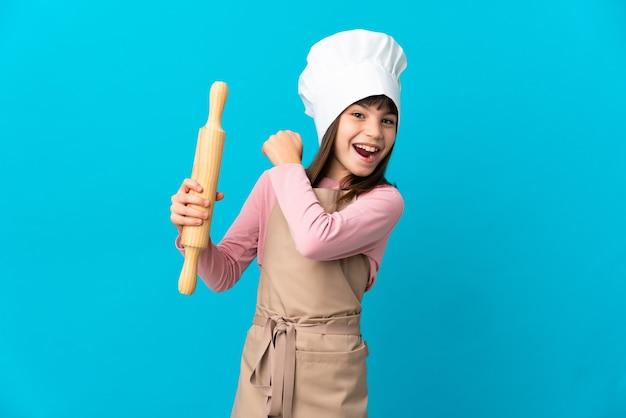 勝利を祝う青い背景に分離された麺棒を保持している少女