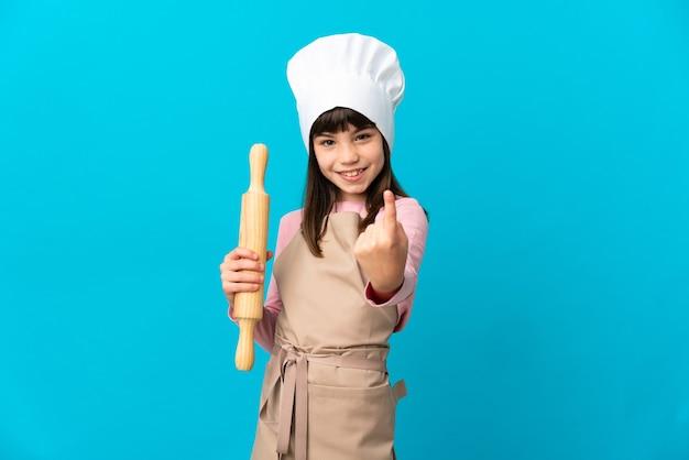 青い背景に分離された麺棒を持って来るジェスチャーをしている少女
