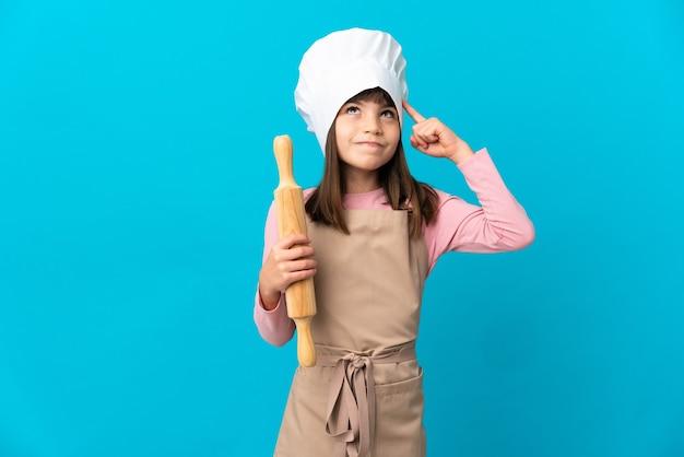 Маленькая девочка держит скалку, изолированную на синем фоне, сомневаясь и думая