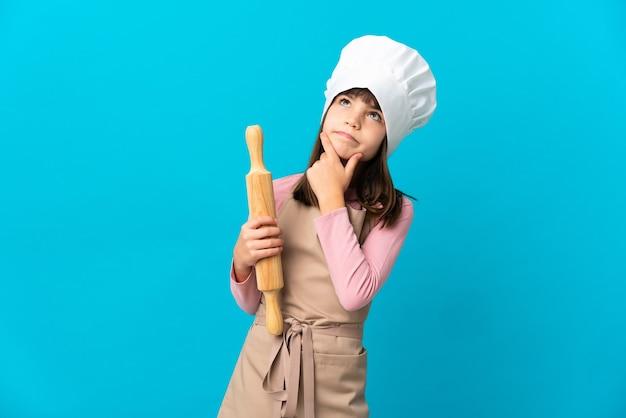 疑いを持っている青い背景に分離された麺棒を保持している少女