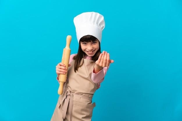 手で来るように誘う青い背景に分離された麺棒を持っている少女。あなたが来て幸せ