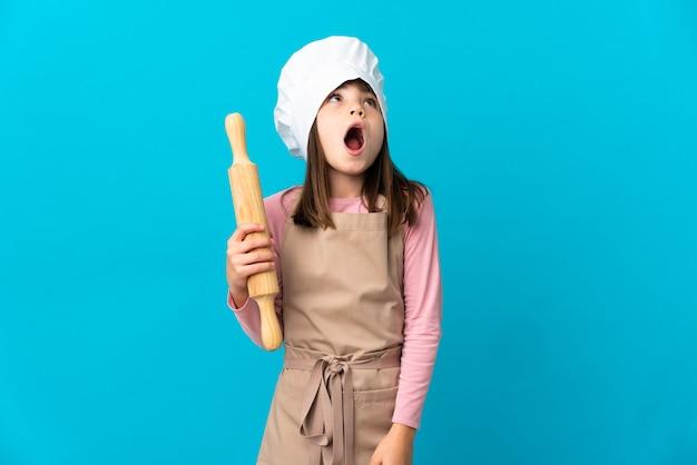 Маленькая девочка держит скалку на синем фоне, глядя вверх и с удивленным выражением лица