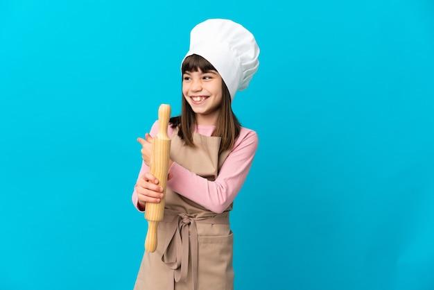 後ろ向きの青い背景に分離された麺棒を保持している少女