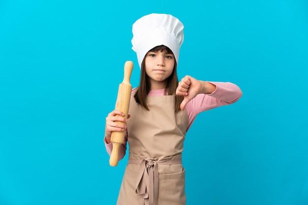 부정적인 표현으로 아래로 엄지 손가락을 보여주는 파란색 배경에 고립 된 롤링 핀을 들고 어린 소녀
