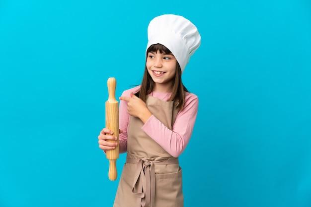 指を持ち上げながら解決策を実現しようとしている青い壁に分離された麺棒を持っている少女