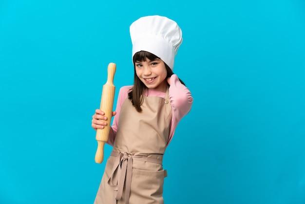 青い壁に分離された麺棒を持って笑っている少女