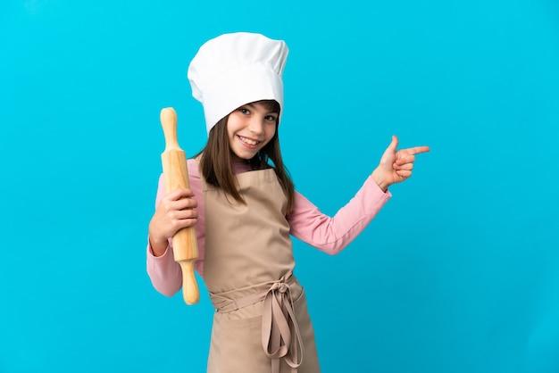 측면에 파란색 벽 가리키는 손가락에 고립 된 롤링 핀을 들고 어린 소녀