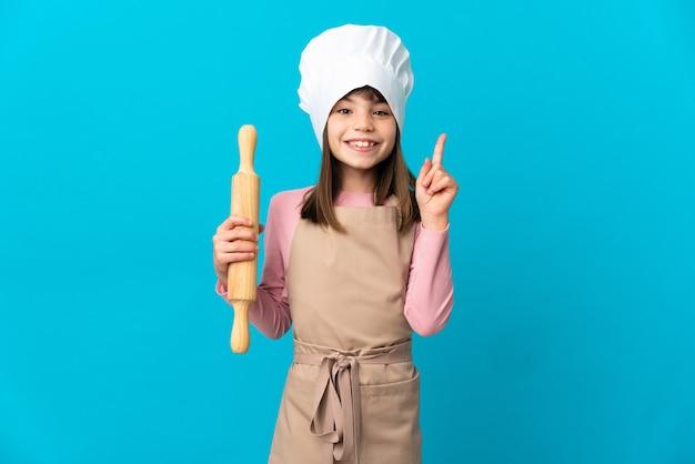 좋은 아이디어를 가리키는 파란색 벽에 고립 된 롤링 핀을 들고 어린 소녀